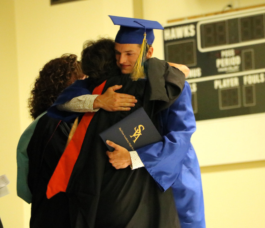 SkyView Academy graduate Christopher Wilhoite embraces his mother, Karen, who is also a teacher and the student selected keynote speaker, at the May 19 commencement ceremony at the school, 6161 Business Center Dr. Wilhoite had to leave the ceremony early to go to a state final in track, so he was the first to graduate.
