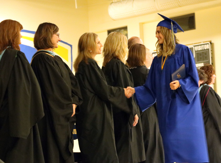 Haley Anderson is greeted by staff of SkyView Academy as she walks across stage to receive her diploma. Anderson was one of 60 seniors to graduate on May 19 in the gymnasium of the school, 6161 Business Center Dr.