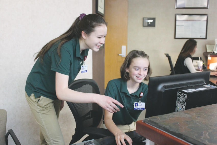 Volunteers at Sky Ridge Medical Center, Aubrey  Stevens, 17, and Eileen Kennedy, 15, spend their Friday evenings manning the front desk, directing foot traffic at the hospital and answering question.