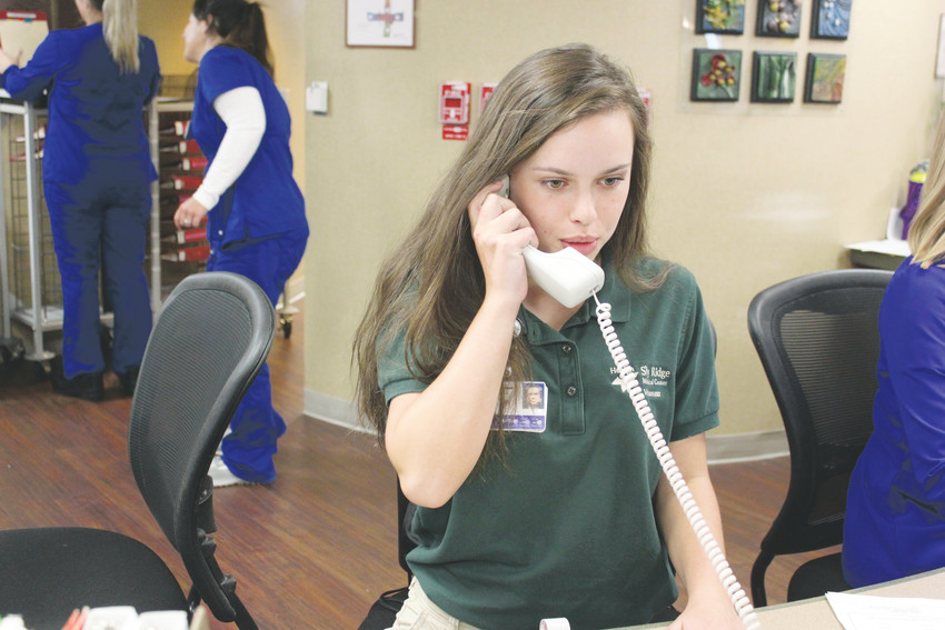 Sky Ridge volunteer Sydney Brennan, 16, spends Friday nights helping nurses on the cardio and neuro floor by answering phones, assembling charts and re-stocking supplies.