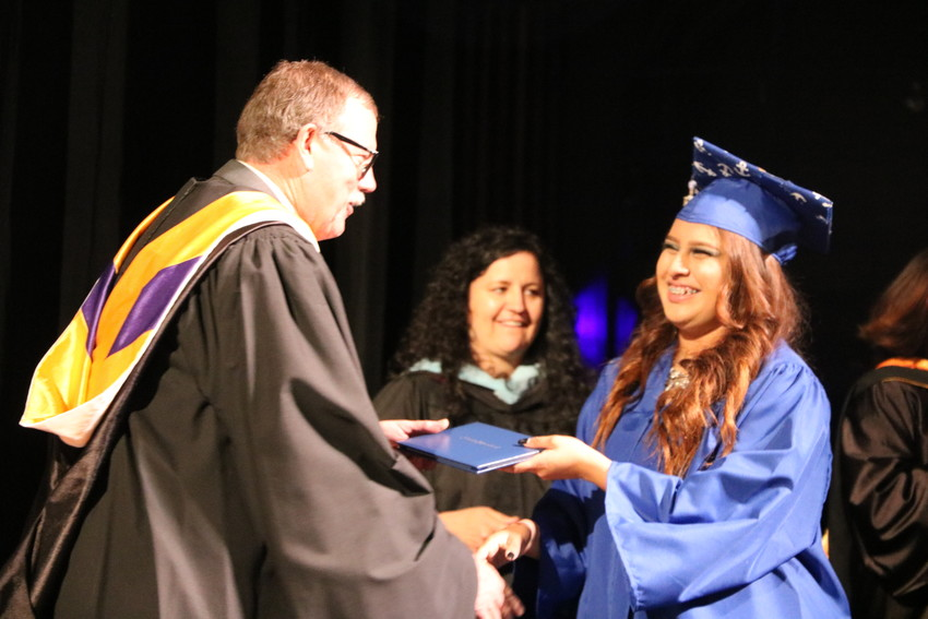 Alameda International High School senior Wendy Giselle Bordallo Rodriguez receives her diploma at the school's graduation ceremony on May 22 at the Buell Theatre in Denver.