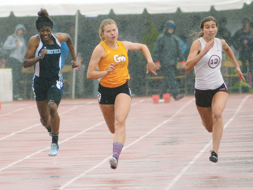 Green Mountain senior Annalie Janus, middle, sprints down the track in the Class 4A girls 100-meter dash state championship race as the rain pours down May 19 at Jeffco Stadium. Janus placed sixth with a time of 12.52 seconds.