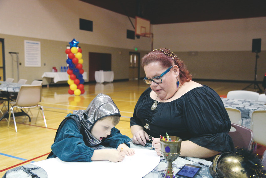 William Matthews, 5, works on decorating his knight's shield with the help of his mother, Debbie Warner.
