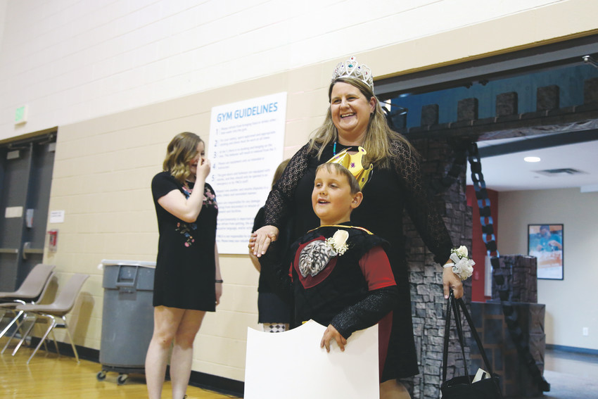 Simon Schrader leads his mom, Megan, into the gym for the Arvada YMCA Mom and Son Date Knight.