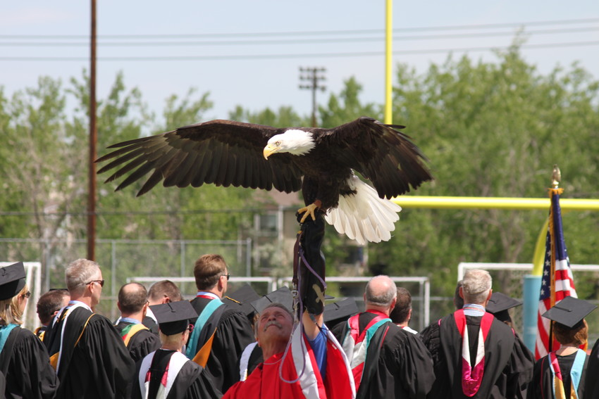 A handler holds a bald eagle, Heritage High School's mascot, aloft at the conclusion of the Star Spangled Banner at the 2018 graduation.