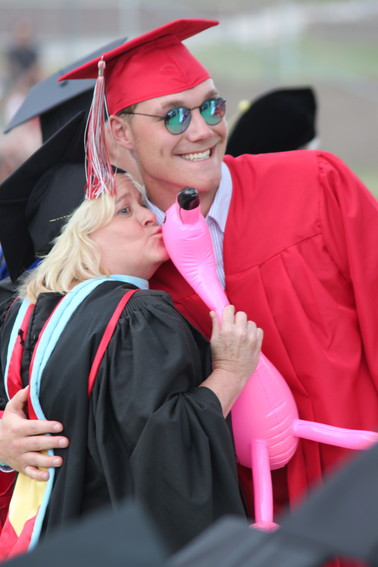 Riley Egloff hugs Heritage High School principal Stacey Riendeau, who smooched an inflatable flamingo in honor of her Florida background.
