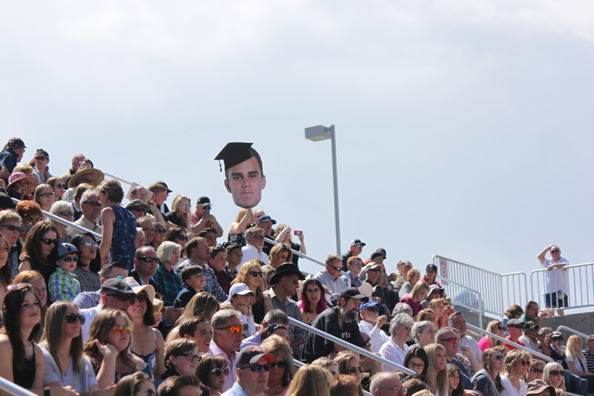 One lucky student's family wanted to make sure he could find them in the crowd, and waved an oversized cutout of their senior throughout the ceremony. Photo by  Tabatha Stewart.