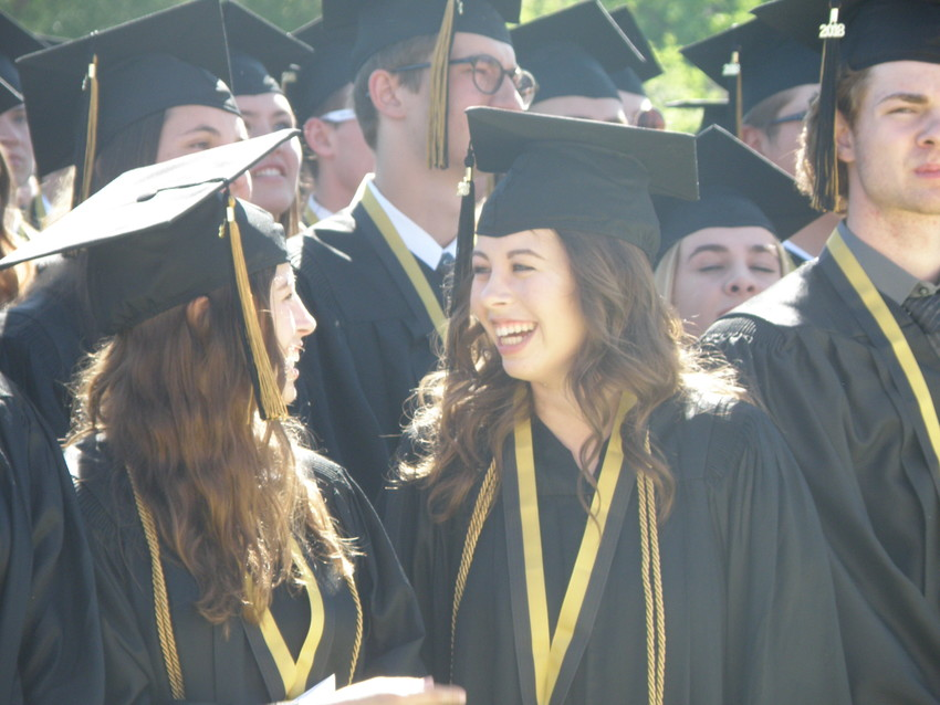 A pair of grads trade grins moments before receiving their diplomas.