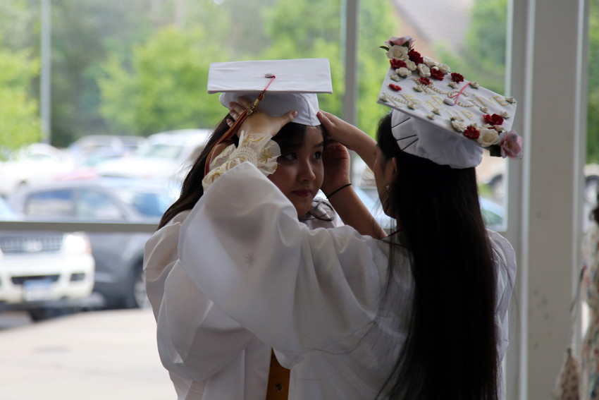 Xinran Li helps her friend Linh Tong with her cap before the Faith Christian High graduation begins.