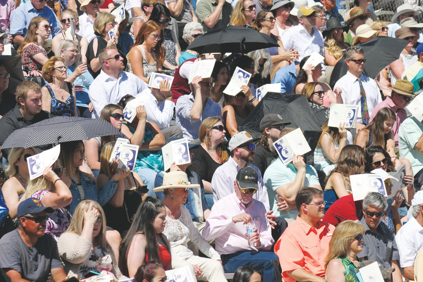 Relatives and friends of graduating seniors used programs to shade themselves from the high-intensity sunshine of a warm Colorado morning at the 2018 Littleton High School commencement ceremony.