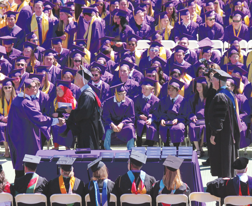 Graduating seniors in a sea of purple robes receive their diplomas at the 2018 Littleton High School commencement ceremony.