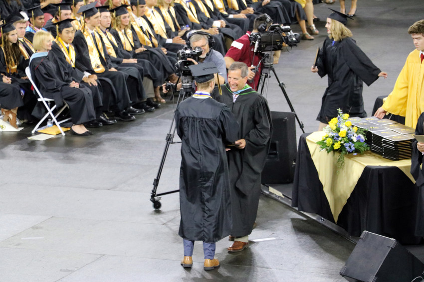 Douglas County School Board member Anthony Graziano congratulates a graduate of Rock Canyon High School at the May 26 commencement ceremony at University of Denver Magness Arena, 2250 E Jewell Ave.