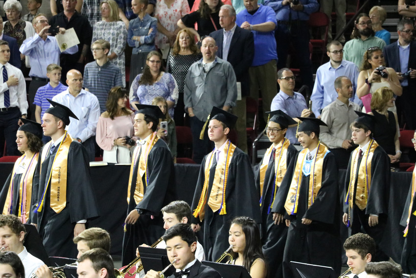 Wearing smiles, graduates of Rock Canyon High School entered University of Denver Magness Arena, 2250 E Jewell Ave, for the 2018 graduation ceremony on May 26.