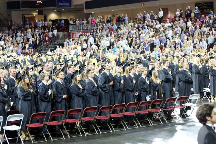 Graduates of Rock Canyon High School stand for the Pledge of Allegiance at the 2018 commencement ceremony on May 26 at the University of Denver Magness Arena, 2250 E Jewell Ave.