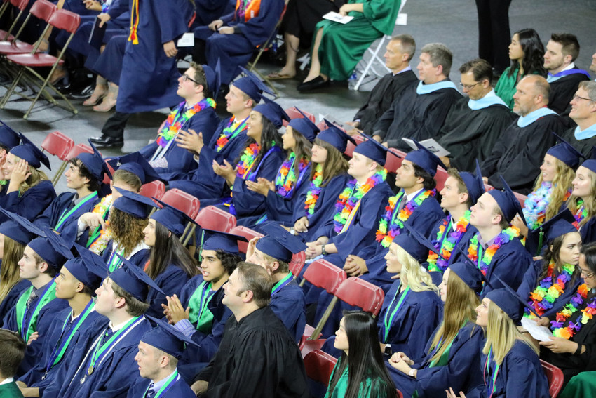 Wearing colorful leis, graduates of ThunderRidge High School listen to speakers at the May 26 commencement ceremony.