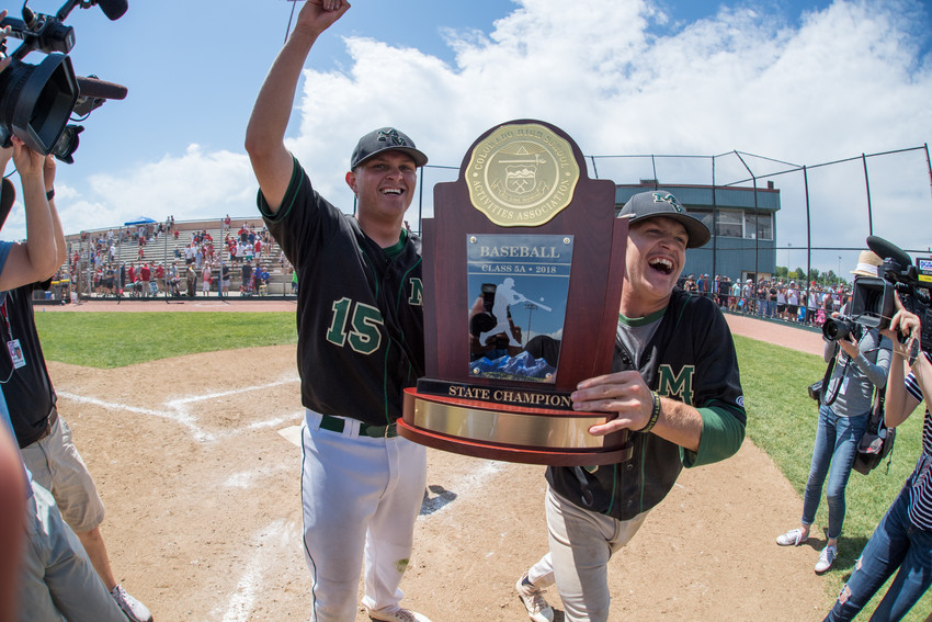 Mountain Vista's Jack Liffrig (15) and Zach Paschke (3) take position of the 5A State Championship trophy and bring back to the team.  The Golden Eagles eliminated Mountain Range earlier in the day 14-4 in five innings and then defeated Heritage 7-2 in the Final.