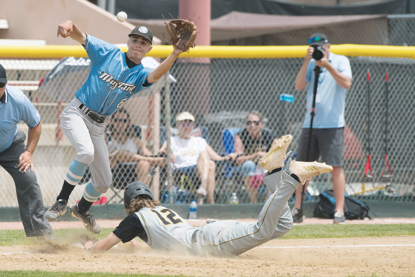 Arapahoe's Cade Segura (12) makes the slide to third base, just beating the throw to Mountain Range's Braden Courter (6).  Arapahoe was eliminated 1-0 from the 5A baseball playoffs May 26 at All City Field in Denver.