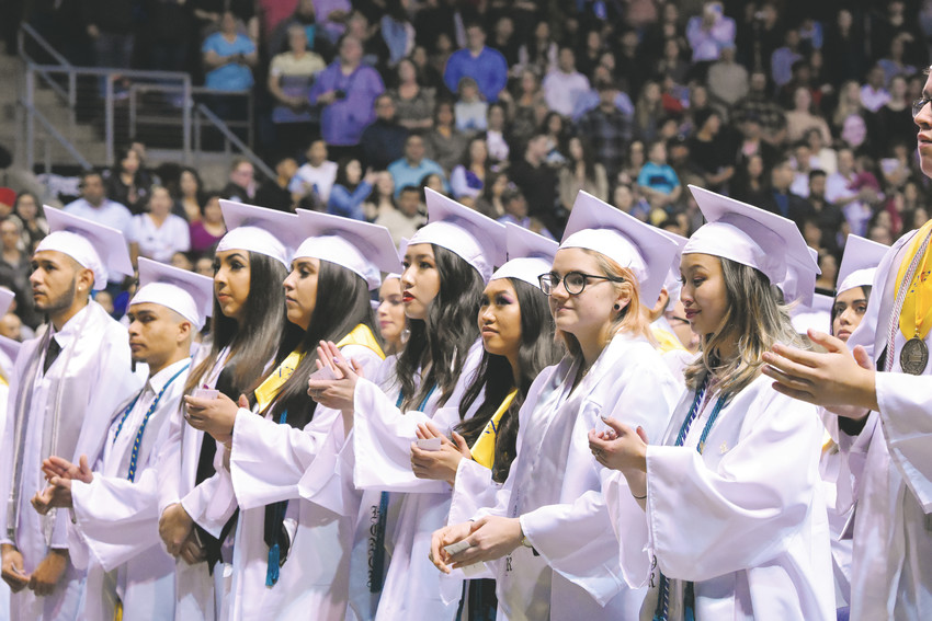 A row of Westminster High School honors graduates applaud during graduation ceremonies May 19 at the First Bank Center in Broomfield.