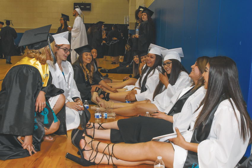 A group of Westminster High School graduates relax on the floor of an auxiliary gymnasium ahead of formal graduation ceremonies May 19 at the First Bank Center in Broomfield.