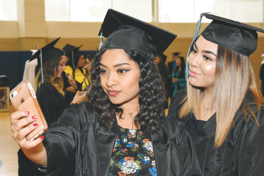 Kimberly Nerio, left, takes a cellphone selfie with classmate Ambriona Luevano, prior to Westminster High School graduation ceremonies held May 19 at the First Bank Center in Broomfield.