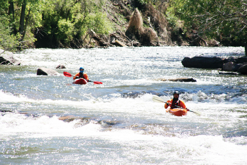 Two kayakers paddle down Clear Creek in Golden during a kayak event last year.