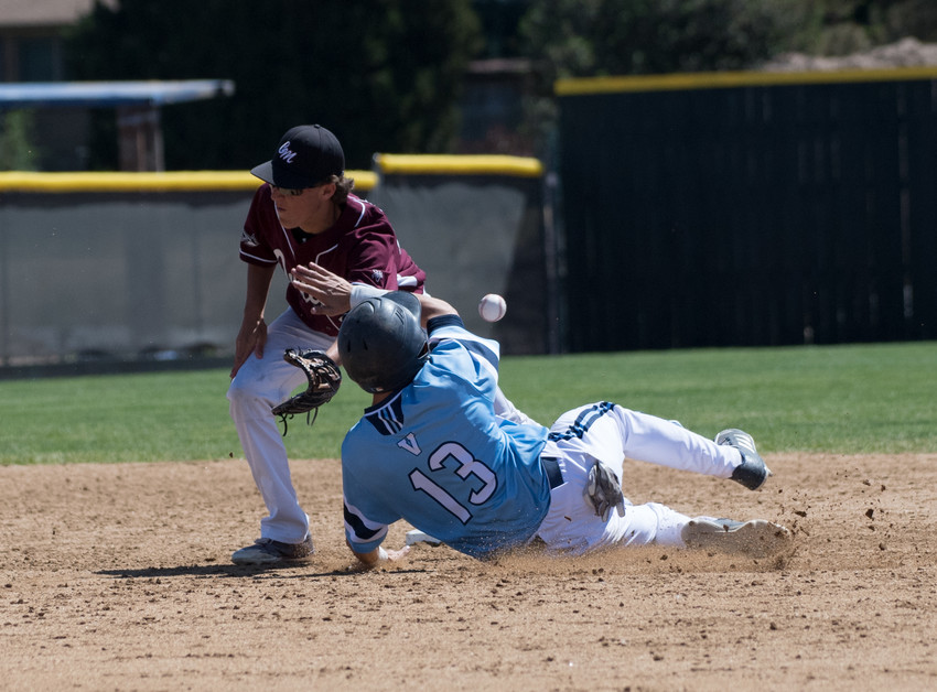 Valor Christian's Brady Buehler (13) makes the successful slide breaking up the play on Cheyenne Mountain's Grant Mondejar (29).