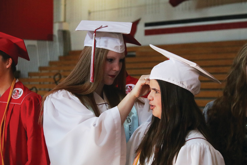 Catherine Witten uses a hairpin to secure classmate Cheyenne Toft's hat to her hair as they prepare for the May 25 graduation ceremonies for the Elizabeth High School Class of 2018. After the 131 graduated had received their diplomas in the school stadium they marched up the steps to the enthusiastic applause of the standing room only crowd of friends and family members.