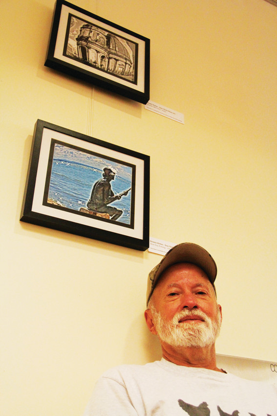 Photographer Dennis Behm stands near his work on display June 1 at the Englewood Public Library. Behm, 65, lives in Englewood and had his first art display at Nixon's Coffee House about three years ago.