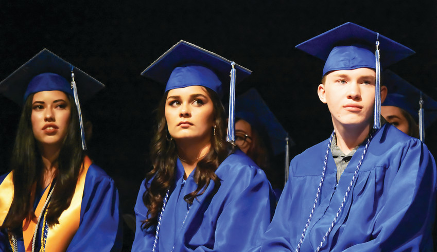Westgate Community School graduates, Caitlin Ryan, left, Kayla Dillinger, and Cian Mitchell, listen to a keynote address by Jason Arneson, during commencement ceremonies held May 29 at Mountain Range High School in Westminster.