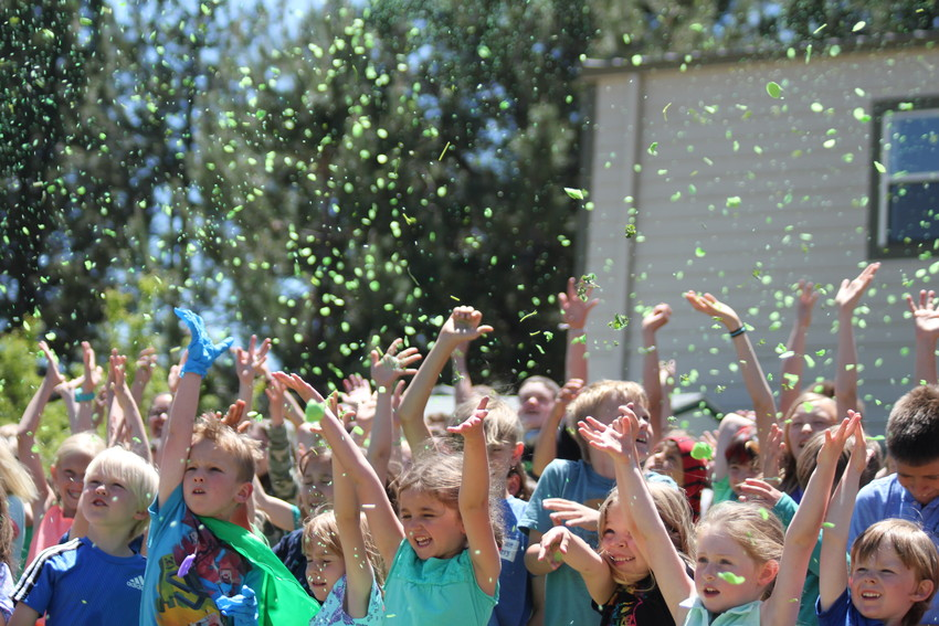 "Students at Mackintosh Academy hurl ""eco-confetti,"" made of parsley and rice, during a ceremony to celebrate becoming a 2018 U.S. Department of Education Green Ribbon School, awarded for the school's environmental sustainability efforts."