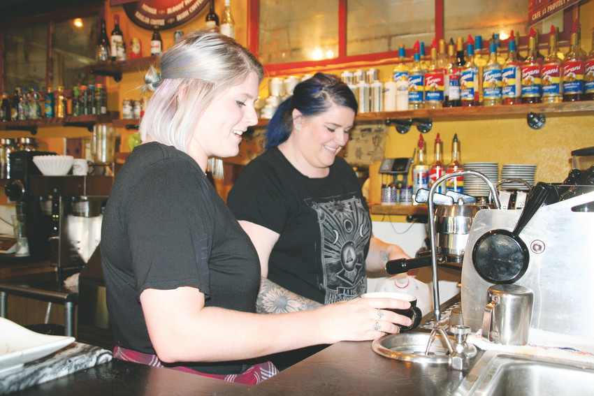 "Café 13 baristas Jo Carswell, front, and Bree Becker make a latte on May 31. The two enjoy their job for the atmosphere and the people they get to meet. ""It's intimate,"" Becker said. ""All the regulars who come in know our names, and we know theirs."""