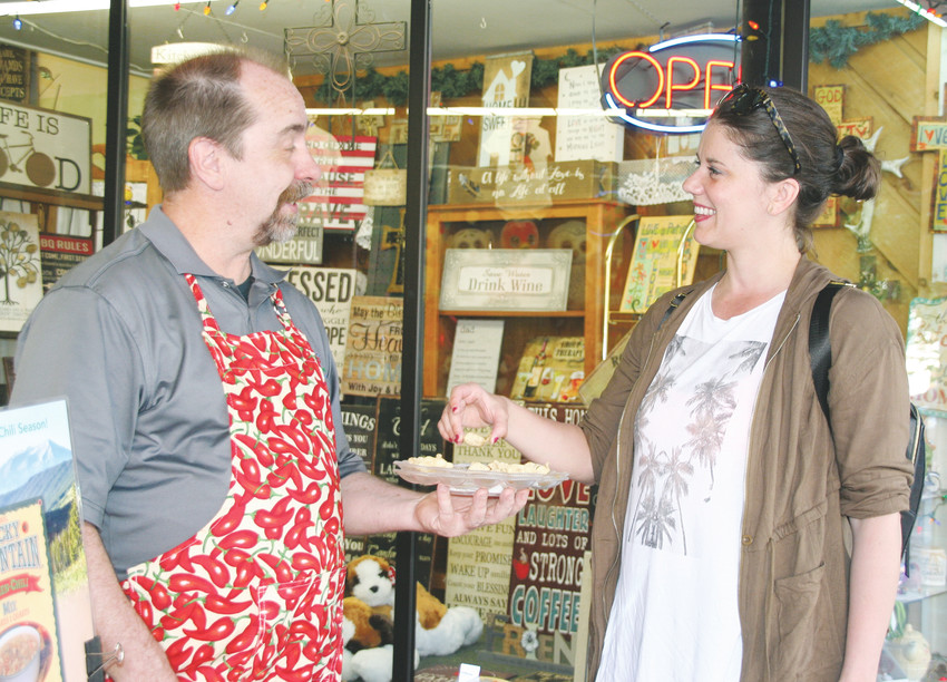 Alyssa Emme, right, who was visiting Golden from Minneapolis for a wedding, accepts a sample of Rocky Mountain Green Chili from Randy English on June 1 during Golden Weekends.