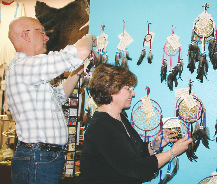 Joe Miklos and Judy Farley, shop owner of Wings of Eagles, organize the dreamcatchers display on June 1. The dreamcatchers were offered at a discount as a special for Golden Weekends.