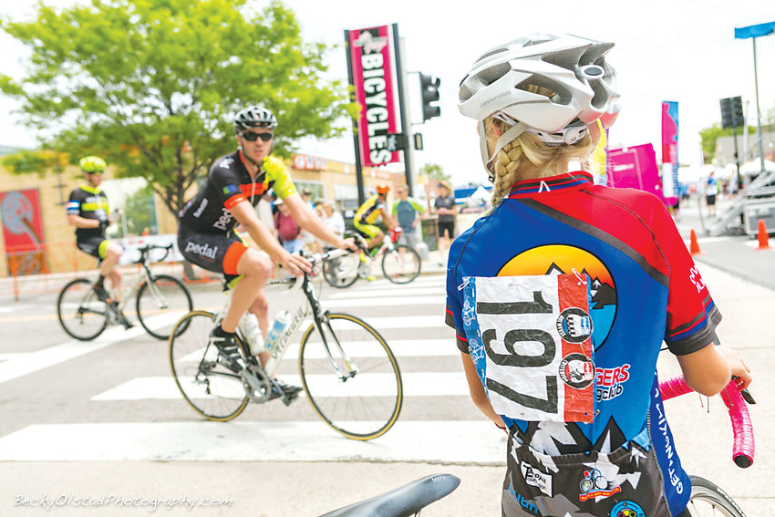 A competitor watches a criterium racer take a turn during last year's Ridge at 38 Criterium in Wheat Ridge.