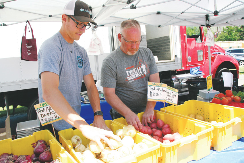 Vincent Domenico, left, and Leonard Walmsley organize some of the organic produce from Platteville's Ray Dominico Farms on June 2 at the Golden Farmers Market.