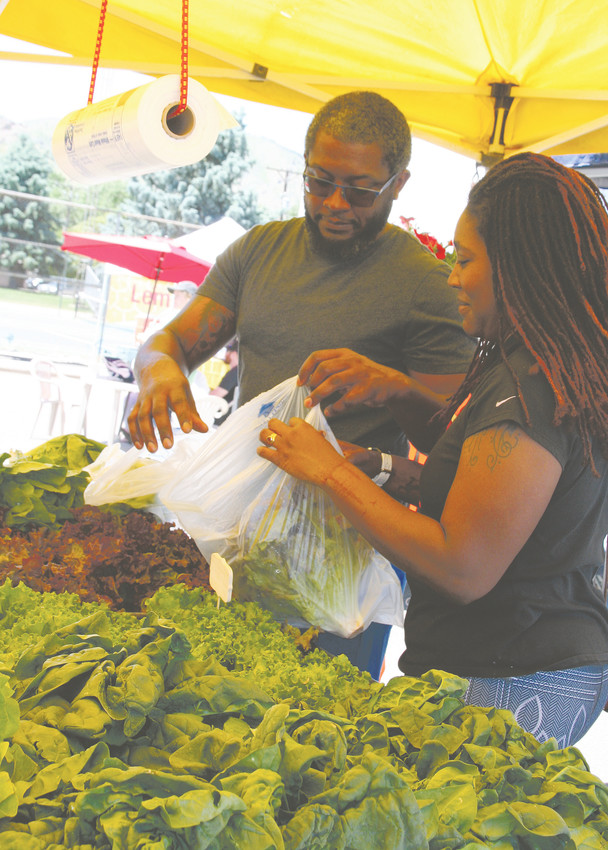 Tasha Steward-Childs and Jeremy Childs of Aurora pick out some leafy greens from the Palizzi Farm stand from Brighton. on June 2 at the Golden Farmers Market.