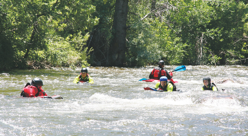 A few first responders part of a training class being put on by Dive Rescue International use a boogie board on June 2 in Clear Creek in Golden as part of a training exercise in moving water while a kayaker also enjoys the river.