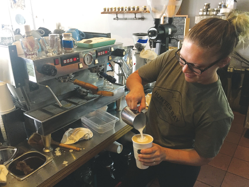 Hunter Bay barista Veronica Carlson puts the finishing touches on a latte at the Olde Town Arvada coffee shop.