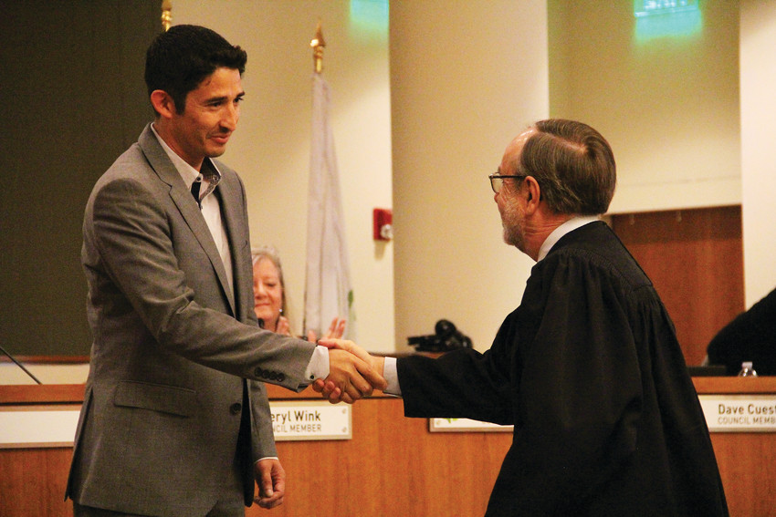 Englewood City Council member Othoniel Sierra, left, shakes hands with Englewood Associate Judge Vincent Atencio June 4 after being sworn into office by Atencio. The ceremony in the Englewood City Council chambers marked the end of a nearly five-month period in which the council operated one member short.