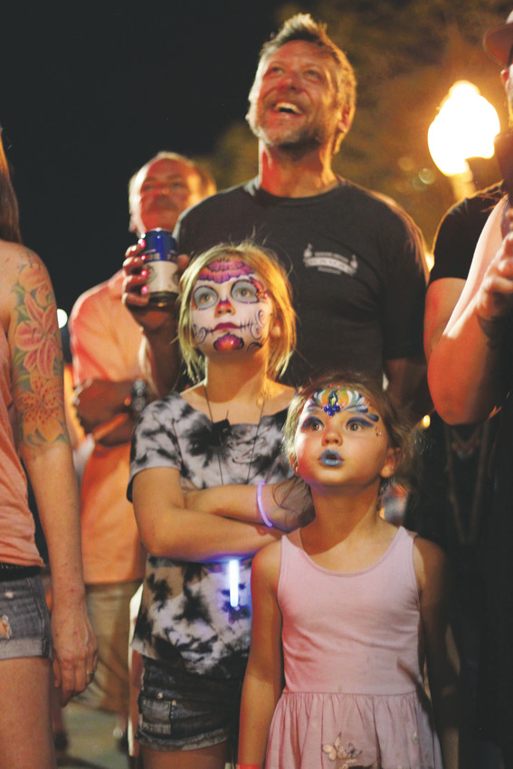 Michael Barger watches fireworks with Zoie Brown, 9, and Emma Brown, 5.