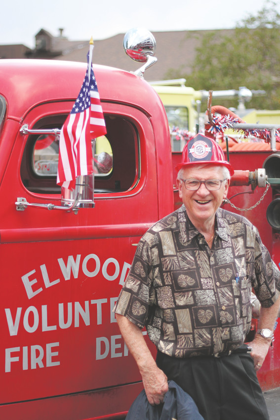 Peter Smaus poses for his wife's camera beside an antique fire truck.