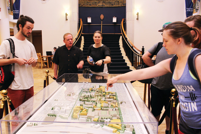 Students look at a model of campus, which shows new buildings included in a new development plan at the University of Denver.