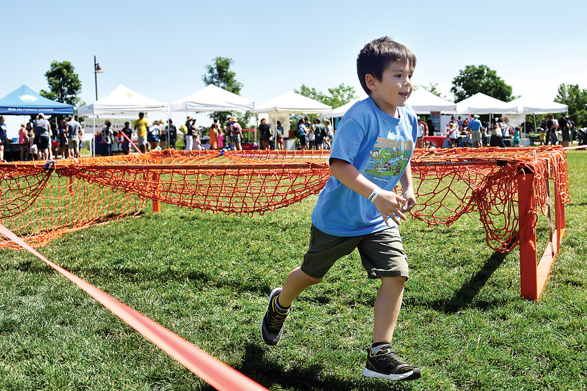 Alyosha Anisimov, 7, runs through a Train OC obstacle course during KidFest June 9 at Civic Green Park. The course included walls, low crawls, cargo nets and balance elements. It was one of the free activities at the Highlands Ranch Metro District event.