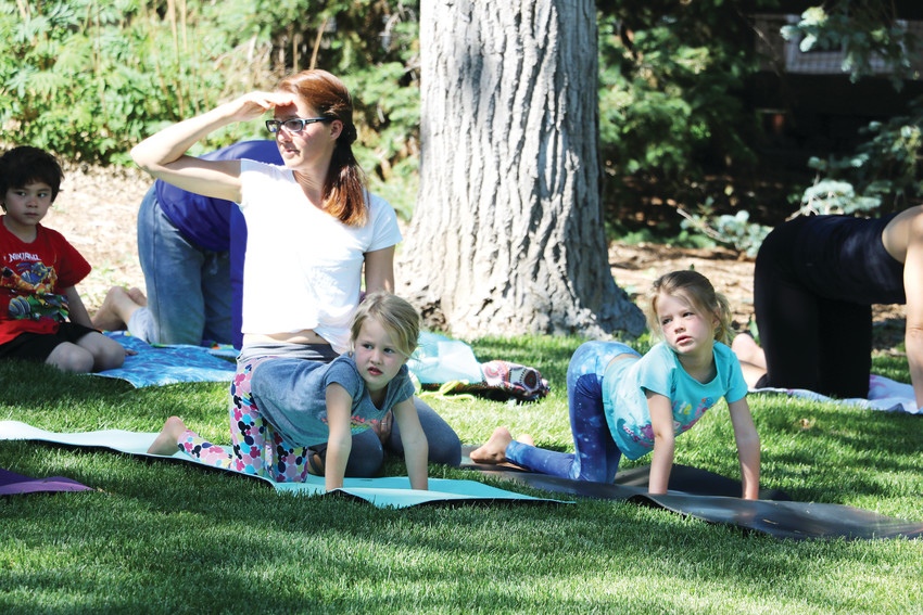 Accompanied by their parents, young boys and girls are led through a series of simple yoga poses at a Young Yogis class on June 8 at Northridge Park, 8800 S. Broadway. The class for ages 6-11 is held Fridays in June from 10-11 a.m.