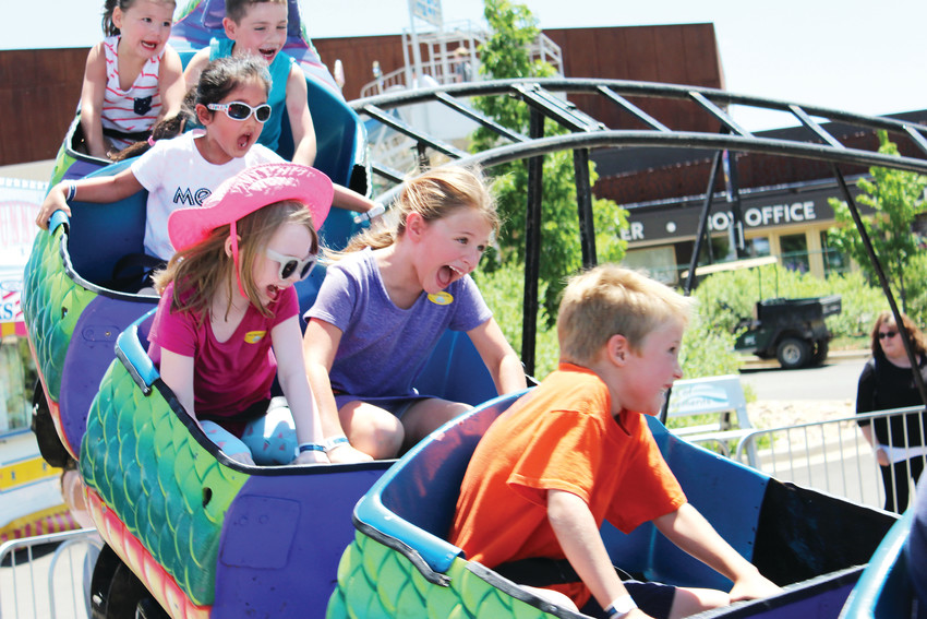 Kids hold tight on a roller coaster June 9 at the 2018 Parker Days festival.