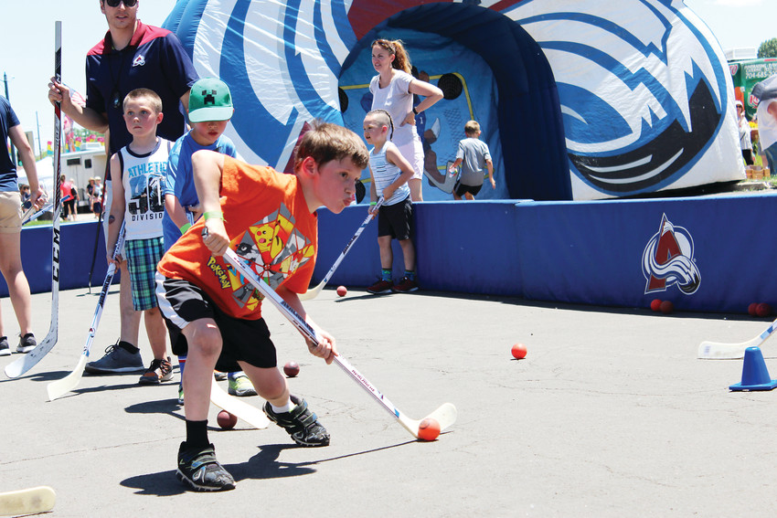 A boy lines up a shot at the 2018 Parker Days Festival's newest attraction, the Colorado Avalanche hockey rink. Each participant learned new stick skills and received a souvenir Avs hockey stick for playing.
