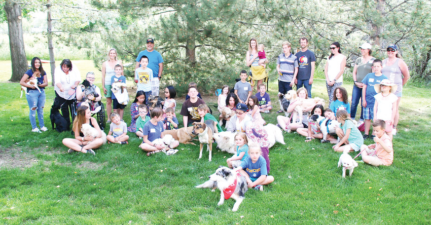 A group of Stink Bug dog recipients gather for a group photo June 7 for a PAWS To Celebrate at KONG Company headquarters in Golden. The event commemorated Stink Bug Project founder Allison Winn's high school graduation and the 100th dog adopted through the program.