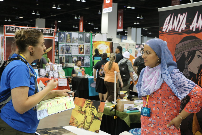 Freelance and comic artist Sanya Anwar visits with a fan at Denver Comic Con on June 15.