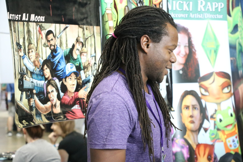 Artist AJ Moore visits with shoppers and shares his art at Denver Comic Con on June 15. Moore was one of hundreds of artists who shared their work with attendees over the weekend.