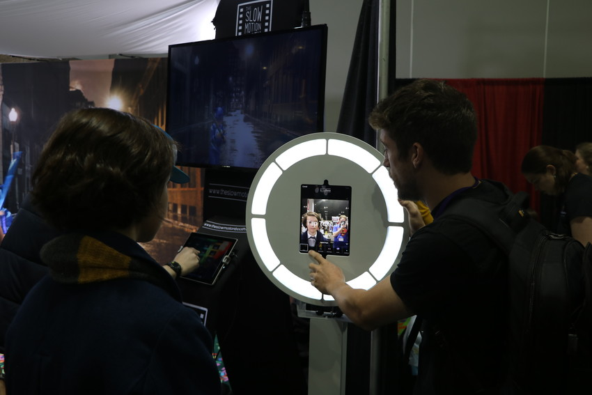 Jeff Libby, booth expert with MiHi Photo Booth, explains how the company's slow motion film booth works at Denver Comic Con.